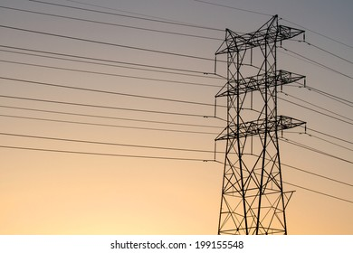 Single electrical power line tower and wires silhouette at sunset.