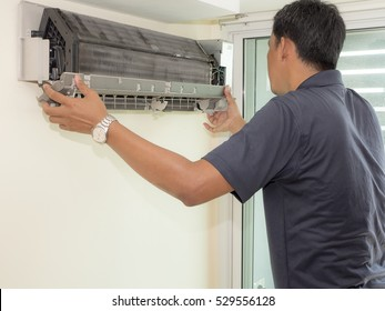 Single electrician man clean, fix and maintain air conditioning in the house
