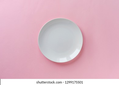 Single empty clean white ceramic plate for the serving of food on a pink background with copy space viewed from overhead