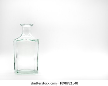 Single empty glass bottle on a white background. Transparent square bottle. Front view of the vertical staying colorless jar.