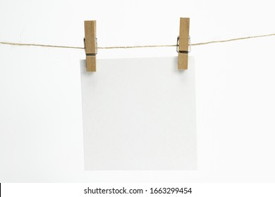 Single empty paper sheet for notes that hang on a rope with clothespins and isolated on white. Blank white cards on rope mockup template.