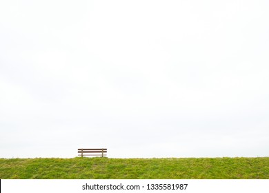 A single empty wooden bench on the horizon above a grass field against a large grey clouded sky depicting loneliness, grieve, being alone, sadness