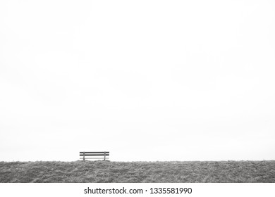 A single empty wooden bench on the horizon above a grass field against a large grey clouded sky depicting loneliness, grieve, being alone, sadness in black and white or monochrome