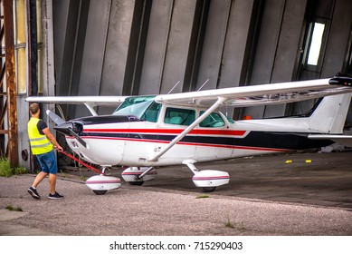 Single engine aircraft, ultra light plane ready for flight. Pilot is pulling out small motor air plane out from hangar in an old airport. Private airport, pilot school. Learning to fly in sunny day
