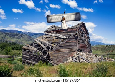 Single Engine Airplane Crashed into a Weathered Old Barn Collapsing Under a Blue Sky in the Old West
