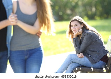 Single envious girl sitting on a bench and seeing an affectionate couple walking in a park