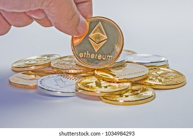 A single Etherium coin on top of a pile of crypto currency.
