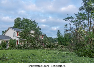 Single family home with roof and gutter damage due to storm.  Many trees blown down.