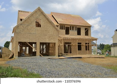 A single family home under construction.  The house has been framed and covered in plywood.  There is a two car garage with a gravel driveway.