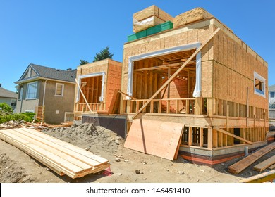 A single family home under construction. The house has been framed and covered in plywood. Stacks of board timber in front and stack of 2x4 boards on the top.