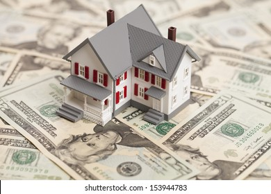 Single family house on pile of money. Concept of real estate.