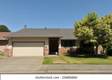 Single family house with one level and a short driveway.
