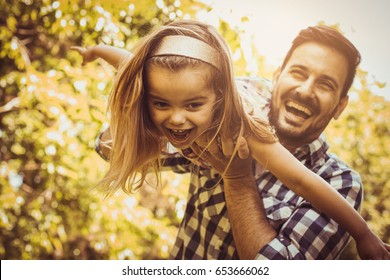 Single father playing in the meadow with daughter. Enjoying in summer day.