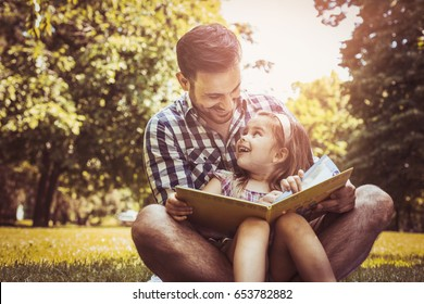 Single father sitting on grass with little daughter and reading book story. Little girl sitting on father lap.