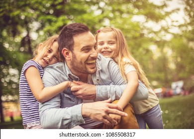Single father spending time at park with daughters.