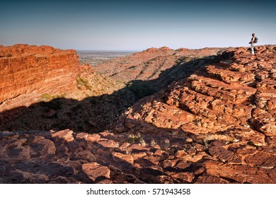 Single female hiker with camera at the top of Kings Canyon in morning light with clear sky