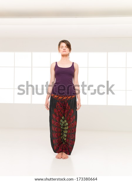 single female in yoga preparatory position at gym in colorful  clothes background window