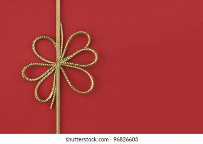 Single festive gold ribbon bow on red background with room for your text