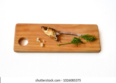 Single fish head with bone on the bread, white background. Poor human diet with green additives.