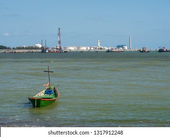 Single fishing boat on the beach with a growing industrial estate in the background in Map Ta Phut, Rayong Province in Thailand