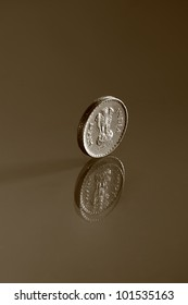 Single five rupee Indian coin and its reflection