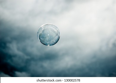 Single floating bubble in front of a dark mysterious sky
