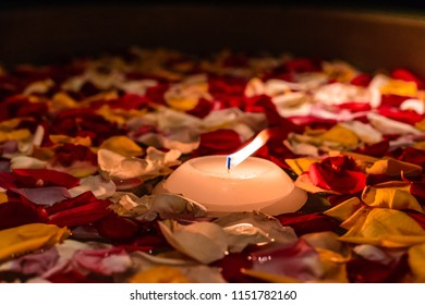 A single floating candle in a pool of dimly lit rose petals on the surface of water.