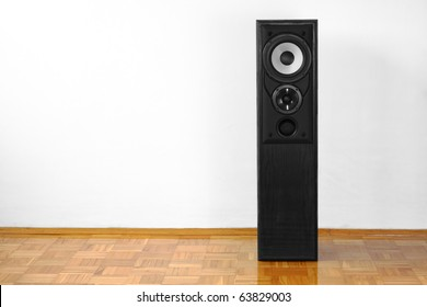 Single floor-standing loudspeaker on hardwood against white wall