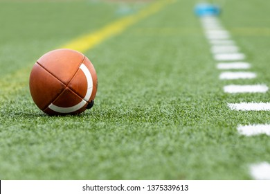 A single football between a yellow and white line on green grass