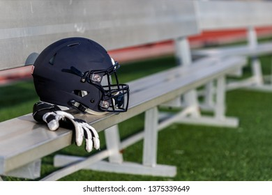 A single football helmet is laying on an aluminium bench