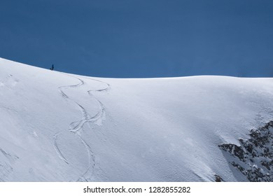 A single freeride skier on a snowy ridge is waiting to drop into  into the Col d'Argentiere, France approach and make his own tracks