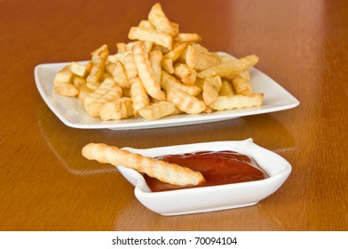 Single french fry in a bowl of ketchup accompanied by a plate full of fries