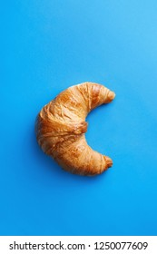 Single fresh croissant isolated on a blue background viewed from above. Top view