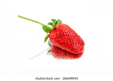 single fresh red strawberry in mirror surface