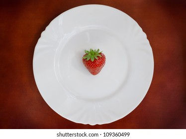 Single fresh strawberry on white plate over brown background