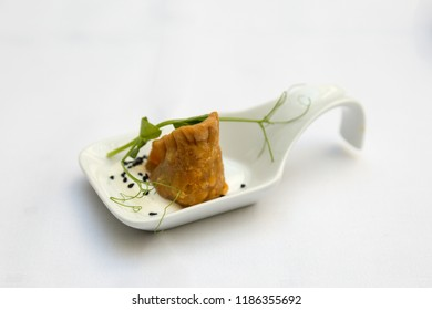 Single fried amuse gueule on white spoon
