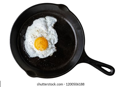 Single fried egg in cast iron frying pan sprinkled with ground black pepper. Isolated on white from above.