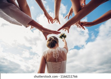 single girls bridesmaids pulling their hands to catch a wedding bouquet of flowers, throwing a bride, wedding tradition, divination, flying a bouquet against the sky, throwing over his shoulder