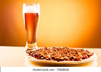 Single glass of beer and pizza over yellow background