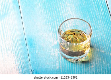 single glass on a blue painted wooden table, in a glass of tequila