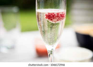 Single glass of prosecco with raspberry