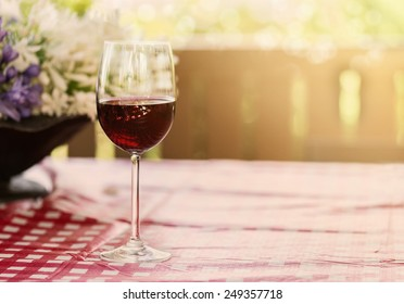 Single glass of red wine over natural background with hazy sunlight and bokeh. Copy space, selective focus, shallow Depth of field