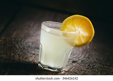 Single glass of vodka with lemon and lemon slice on an old dark wood background, dark toned image, selective focus