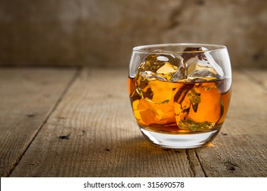 Single glass of whisky bourbon on the rocks golden on old rustic wooden surface open space