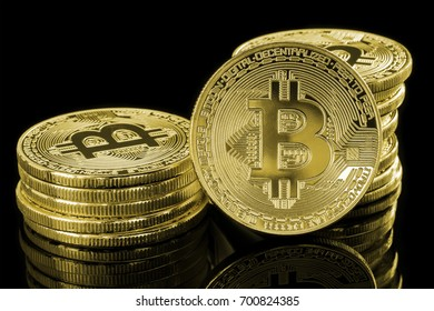 Single golden Bitcoin in front of two stacks of golden coins isolated on a reflective, black background. Conceptual image to visualize cryptocurrency.