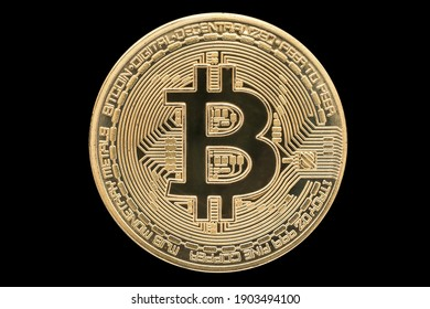 Single golden bitcoin isolated on black background