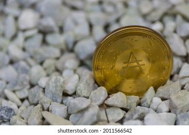 single golden shining ada coin from cardano currency standing in a gravel front right
