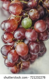 A single green grape stands out among a bunch of red grapes