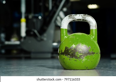 Single green kettlebell on the gym floor ready to use for strength and conditioning training sport concept
