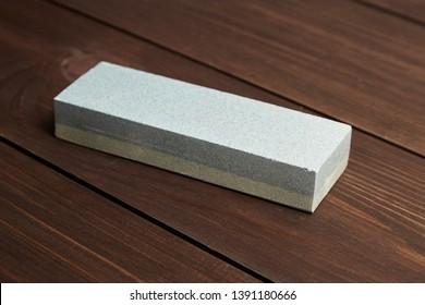 Single grindstone or whetstone sharpener on wooden table background. Rectangular double layer sharpening stone